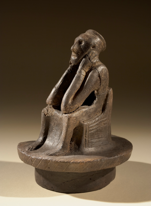 An Anglo-Saxon urn lid in the form of a seated figure.
